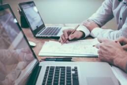 Zwei Personen prüfen aktuelle Nachträge von der Baustelle (Claim Management).